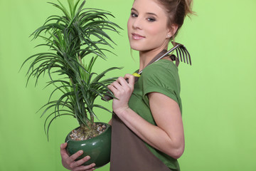 Young woman holding a plant