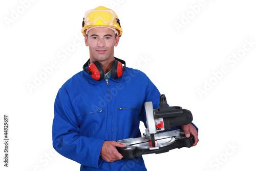 Tradesman holding a mitre saw