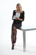 Blond office worker perched on desk