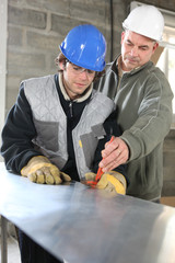 Apprentice  and foreman on construction site