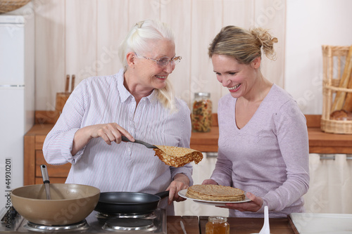 Mother and daughter cooking pancakes