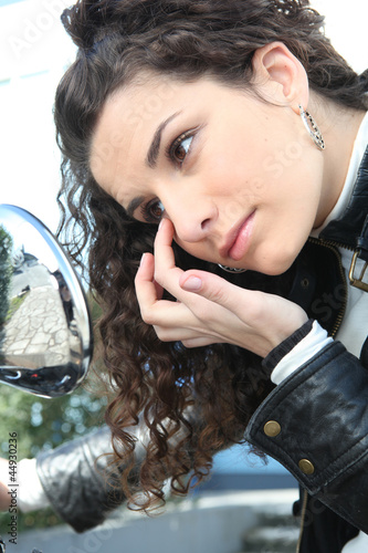 woman looking her eye in the rearview mirror