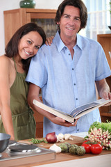 Couple in kitchen with cookbook