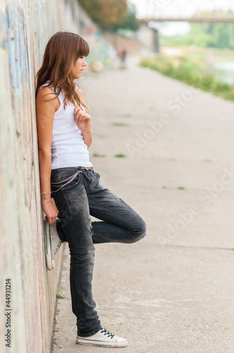 Lonely teenage girl leaning against concrete wall
