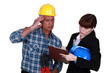 Confused tradesman watching an engineer writing on a clipboard