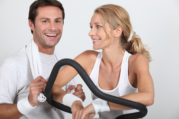 Couple at the gym on cycling machine