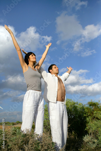 Couple stood in a field with their arms raised