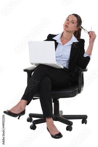 businesswoman sitting on chair with laptop