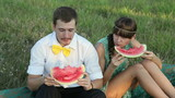 Young couple eating watermelon at picnic