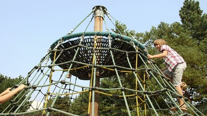 Kid climb on rope lattice at playground