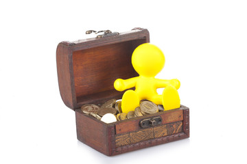 toy yellow little man sits on a chest with money