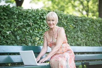 Rentnerin mit Laptop auf Parkbank