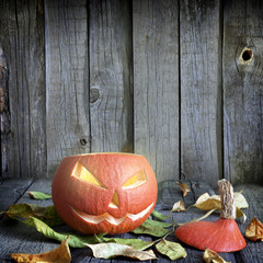 Halloween pumpkin on old grunge boards with leaves background