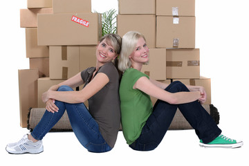 Smiling women sitting in front of stacks of cartons