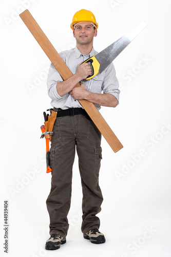 Carpenter with plank and saw