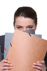 Businesswoman hiding face behind folders