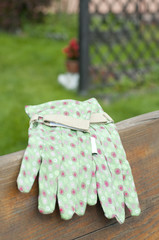 Green garden gloves on bench