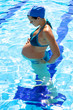Gorgeous pregnant female model in swimmingpool looking belly