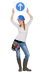 Female builder in studio holding road sign