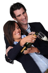 Happy couple pouring champagne
