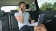Busy businesswoman with laptop and mobile phone in car