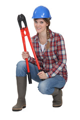 Woman crouching with bolt cutters