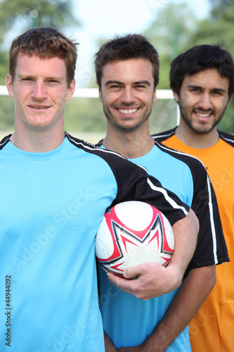 Three smiling young football players