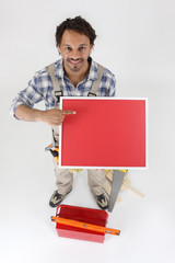 Carpenter pointing at red panel