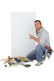 Handyman pointing to a blank sign