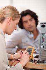 Young woman repairing computer