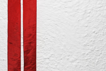 white wall with two red ribbons looking like an austrian flag