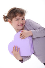 Adorable girl hugging a heart-shaped box