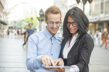 Businesspeople on street - man and woman with tablet computer