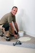Smiling carpet fitter spreading adhesive on an old tiled floor