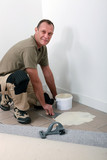 Smiling carpet fitter spreading adhesive on an old tiled floor poster