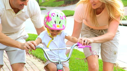 Young Parents Supporting Toddler on Little Bicycle