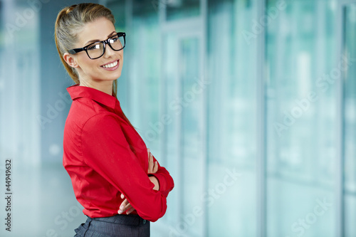Young businesswoman against office windows.