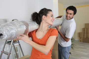 Couple carrying new rolled-up carpet in to house