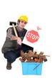 Builder kneeling by recycle box