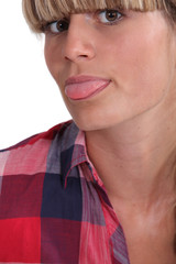 Closeup of young woman sticking her tongue out