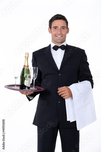 Smart waiter holding tray of champagne glasses