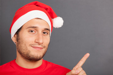 Young Man with Santa Hat Pointing Copy Space