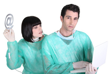 doctor and nurse holding a laptop and an at sign