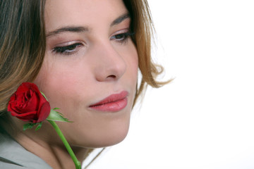 Pensive woman with red rose