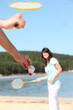 Man and woman playing badminton on the beach