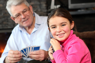 Young girl playing cards with grandpa