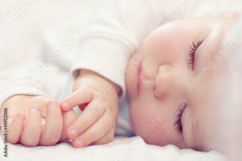Leinwanddruck Bild close-up portrait of a beautiful sleeping baby on white
