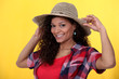 Cheerful brunette wearing straw hat