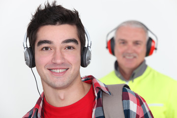 Student wearing headphones in front of a worker