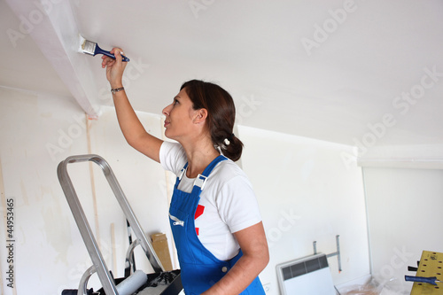 Young woman repainting ceiling